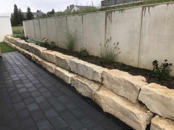 Natursteinmauer an einer Stützmauer mit beischen Steinen